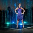 Beautiful girl dancing at outdoor water fountain in a night - Stock Photo