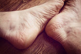 Two grunge foots on a wooden floor — Stock Photo