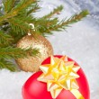 Christmas ball and heart in a gift — Stockfoto