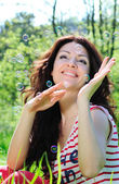 Beautiful woman catches soap bubbles — Stock Photo