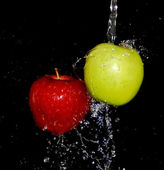 Two apples red and green in water on a black background — Stock Photo