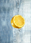 Lemon in water on a blue background — Stock Photo