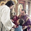 Orthodox bishop gives communion to a little boy — Stock Photo
