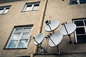 Four antennas on the beige wall — Stock Photo