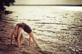 Sporty woman doing stretching exercise on the bank — Stock Photo