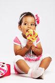 Lovely little girl eating a big lollipop — Stock Photo