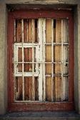 An old damaged window behind metal grating — Stock Photo