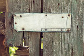 An old corroded banner on grungy wooden fence — Stock Photo