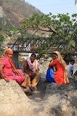 Three seated women in bright saris — Stock Photo