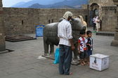 Children are photographed near the sacred cow.Temple of Shiva (Gauri-Shankara) in Naggar — Стоковое фото