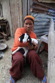 A young woman (Tibetan women) holding a white young goat with black ears — ストック写真