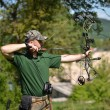 Modern bow hunter in the woods - Stock Photo