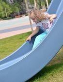 Una bambina giocando in un parco giochi — Foto Stock