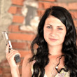 Attractive young woman with a gun - Stock Photo