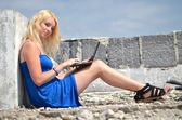 Young pretty woman with laptop on roof — Stock Photo