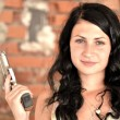 Attractive young woman with a gun — Stock Photo