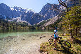 Yaung woman riding a bike beside Alpine lake — Stock Photo