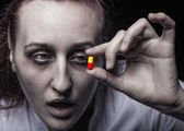 Young woman holding a pill addict. — Stock Photo