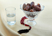 Dates, water and prayer beads — Stock Photo