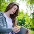 Girl working on a tablet in the green park summer — Stockfoto