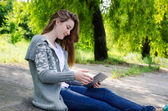 Girl sitting outdoors using a touchscreen tablet — Stock Photo