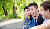 Row of friends sitting together on the park — Stock Photo