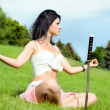 Beautiful woman meditates on green lawn — Stock Photo