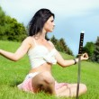 Beautiful woman meditates on green lawn - Stock Photo