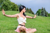 Attractive youngl woman meditates on green lawn — Stock Photo