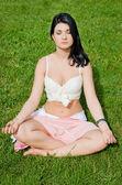 Beautiful woman meditates on green lawn in park — Stock Photo