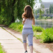 Royalty-Free Stock Photo: Young woman jogging alongside a river