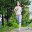Young woman jogging through a park — Stock Photo
