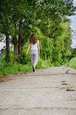 Młoda kobieta spacerowe obok — Zdjęcie stockowe