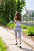 Genç kadın bir nehrin koşu — Stok fotoğraf