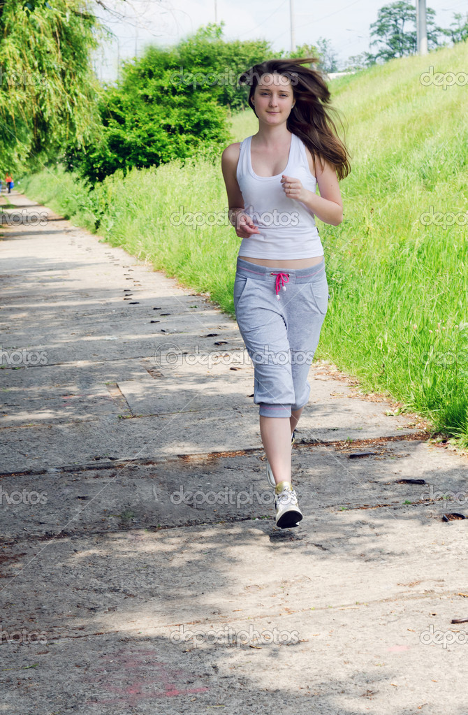 Woman in casual clothes jogging a path through a park as she takes her daily exercise to keep fit — Stock Photo #11352082