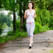 Girl jogging through a park - Stock Photo