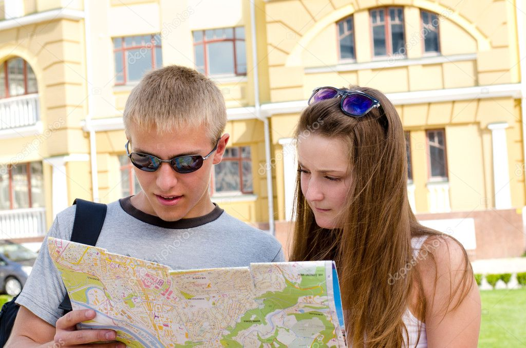 Young couple of tourists consulting a map while sightseeing in an urban environment in summer sunshine  Stock Photo #11909556