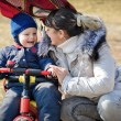 Mother helping toddler ride tricycle — Stock Photo