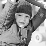 Kid in a jacket on a children's playground autumn — Stock Photo