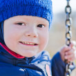 Smiling nice boy on a swing — Stockfoto