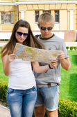 Young couple looking at tourist map — Stock Photo