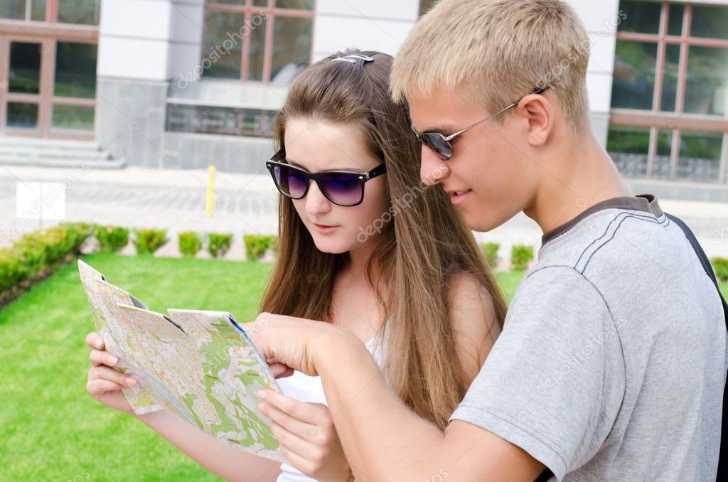Young man pointing out a travel location on a map to his female travelling companion as they enjoy sightseeing on their summer vacation — Stock Photo #11936876