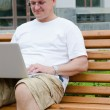 Man sitting on wooden bench using a laptop — Stock Photo #11989980