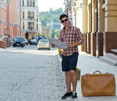 Male tourist with a suitcase and map — Stock Photo