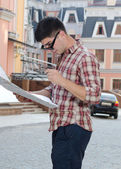 Man looking at a map in town — Stockfoto