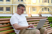Man using his laptop in town — Stock Photo