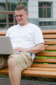 Man sitting on wooden bench using a laptop — Stock Photo