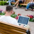 Man using a laptop in a public park — Stock Photo