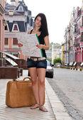 Frau tourist mit gepäck und karte — Stockfoto
