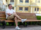 Man sitting waiting on an urban bench — Foto de Stock